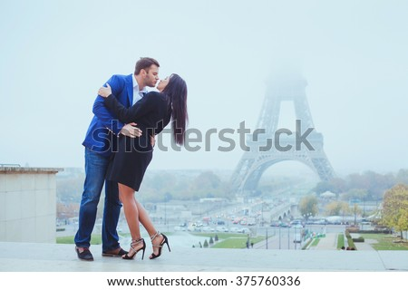 couple kissing near Eiffel Tower in Paris, valentines day destination in Europe, city of love