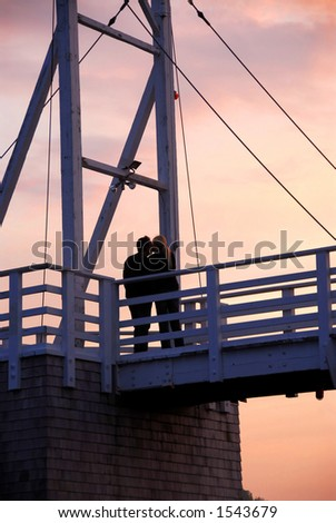 Couple kissing on pedestrian bridge at sunset  in Perkins Cove, Maine - stock photo