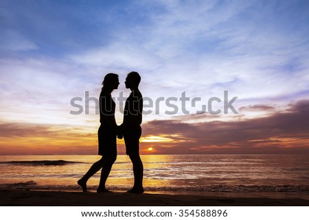 Couple kissing on the beach with a beautiful sunset in the background - stock photo