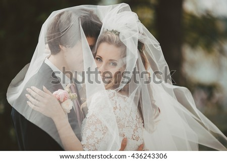 couple kissing under a white veil