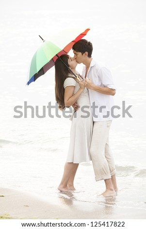 Couple kissing under umbrella at the beach - stock photo