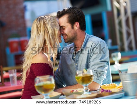 couple kissing while on date at taco restaurant