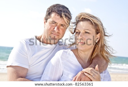 couple laughing in romantic embrace on the beach