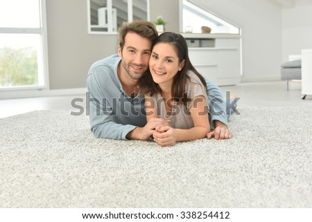 Couple laying on carpet in living room - stock photo