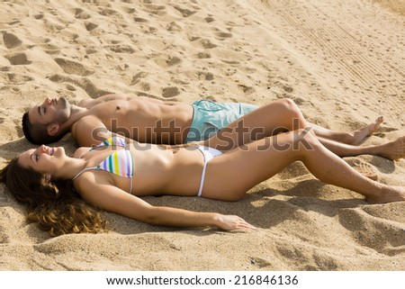 couple laying on sandy beach at sea shore in sunny day