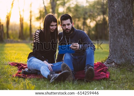 Couple learning with tablet PC in spring park