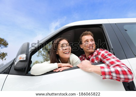 Couple lifestyle in new car looking out window. Driving young man and woman enjoying view on travel road trip in new car. Beautiful young multiracial young couple. Asian woman, Caucasian man.