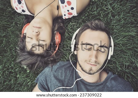 Couple listening to music on headphones - stock photo