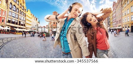 Couple listening to the music, over urban background - stock photo