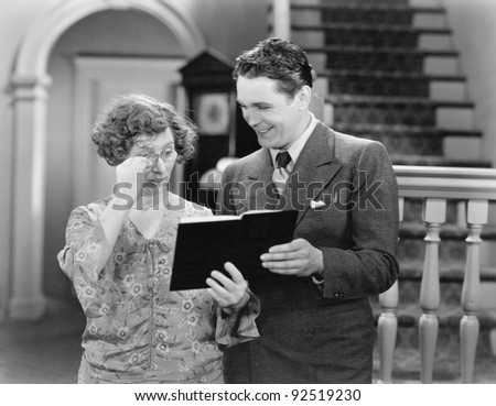 Couple looking at a book together - stock photo