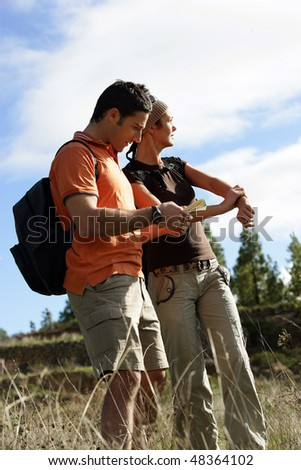 Couple looking at a map on a hiking day - stock photo