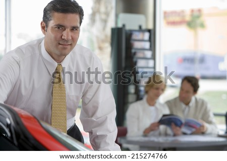 Couple looking at brochure in car showroom, focus on salesman in foreground, smiling, portrait - stock photo