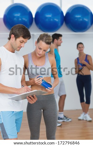 Couple looking at clipboard with fitness class in background at the gym - stock photo