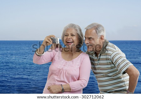 Couple looking at photographs in a camera
