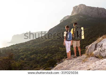 Couple looking at sunrise above the sea from high mountain