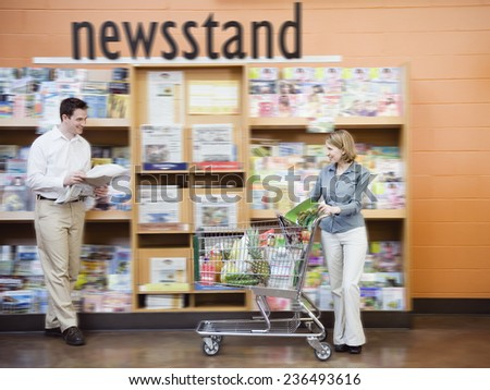 Couple Looking at Supermarket Newsstand - stock photo