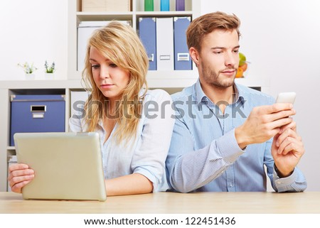 Couple looking at tablet computer and smartphone seperately in living room - stock photo