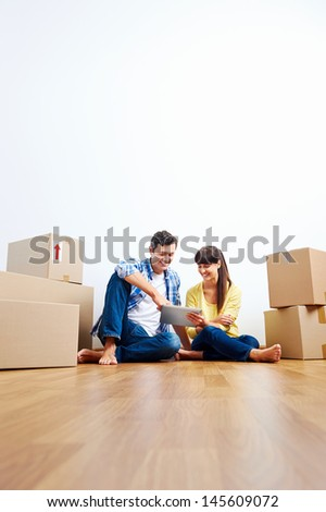 couple looking at tablet while moving into new home with boxes - stock photo
