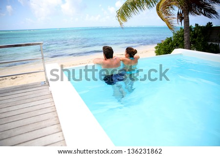 Couple looking at the sea from swimming-pool - stock photo