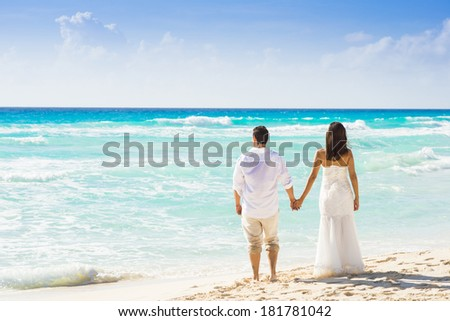 Couple looking at the sea in wedding clothing