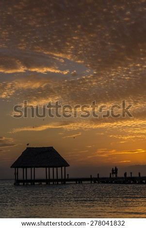 Couple looking at the sun going down on a wooden pier with a hut.