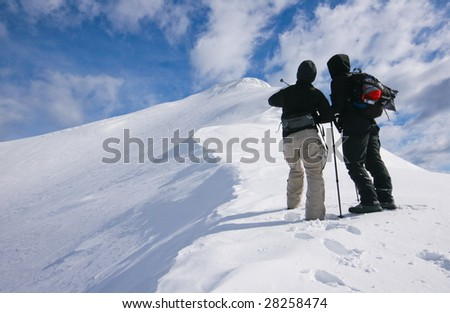 Couple looking at the top of the mountain in alps - stock photo