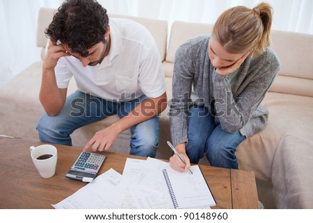 Couple looking at their bills in their living room - stock photo
