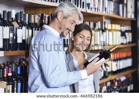 Couple Looking At Wine Bottle's Label
