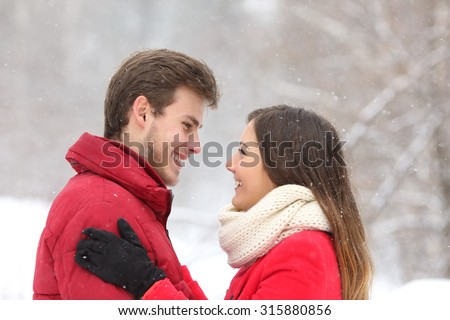Couple looking each other in winter snowing in the mountain