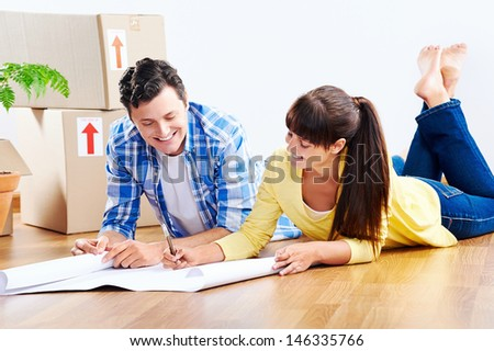 couple looking over plans to new house together lying on wooden floor - stock photo