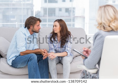 Couple looking to each other during therapy session while therapist watches - stock photo