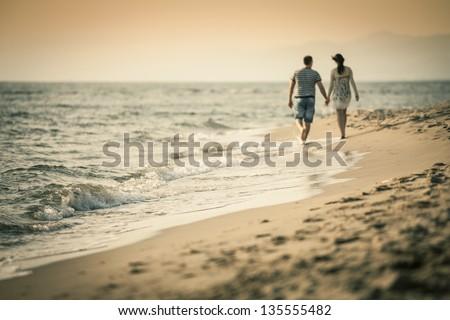 Couple Lovers walking on the beach - stock photo