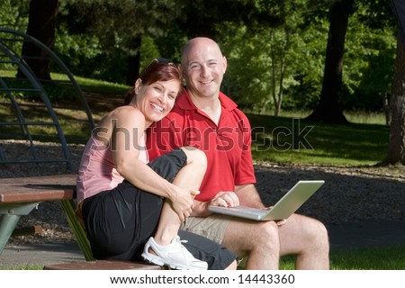 Couple lovingly sitting on a picnic table smiling and sitting at the park. The man is holding a laptop computer. Horizontally framed shot. - stock photo