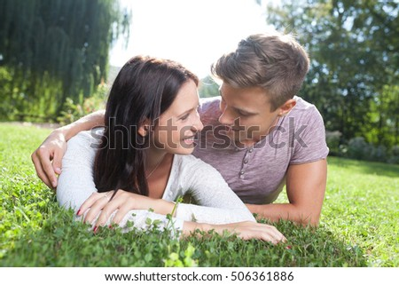 couple lying at grass in park in summer