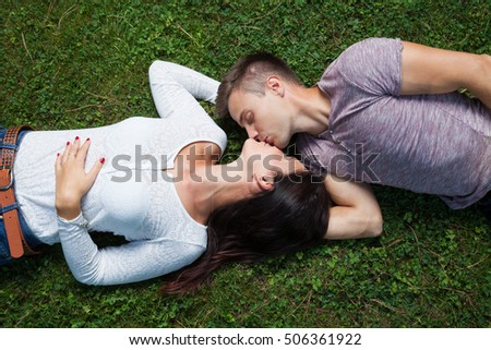 couple lying at grass, kissing