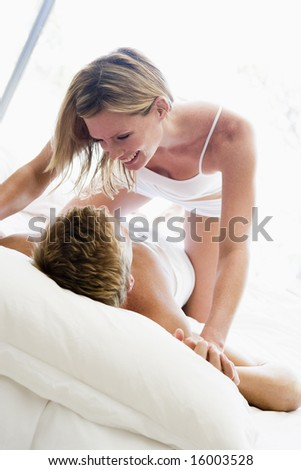 Couple lying in bed being playful and smiling - stock photo
