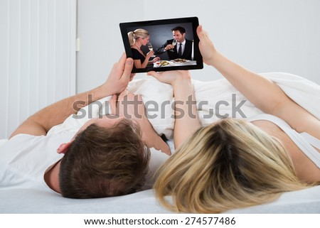 Couple Lying In Bed Watching Video On Digital Tablet - stock photo