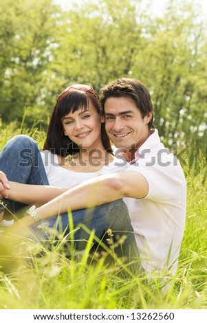 Couple lying in grass, smiling and hugging - stock photo
