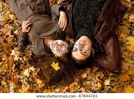 Couple lying in the park in fall. - stock photo