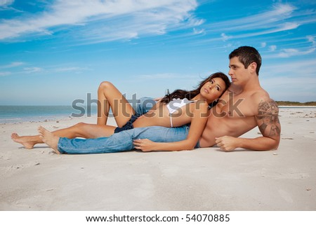 Couple lying on a beach, woman in from of man