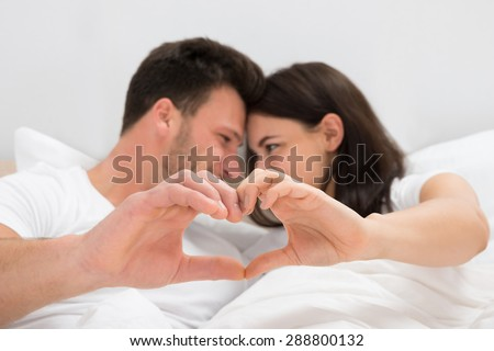 Couple Lying On Bed Forming Heart Shape With Hand - stock photo