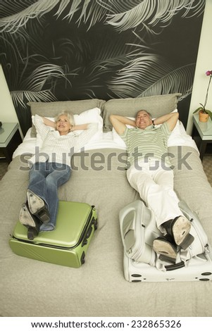 Couple Lying on Bed in Hotel Room with Feet Up on Suitcases - stock photo