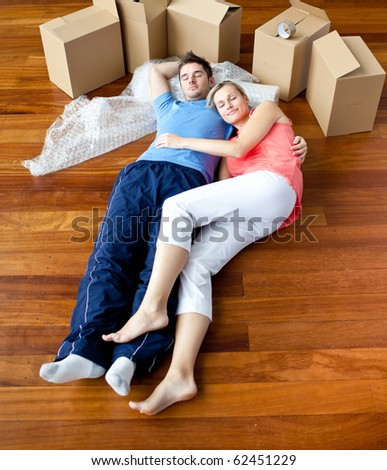 Couple lying on floor by close boxes in new home smiling - stock photo