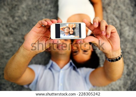 Couple lying on the carpet and making selfie photo on smartphone. Focus on smartphone - stock photo