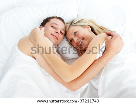 Couple lying together in bed and smiling at the camera