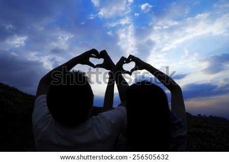 Couple making heart shape with hands against blue sky or blue hour - stock photo