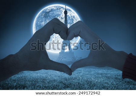 Couple making heart shape with hands against large moon over paris - stock photo