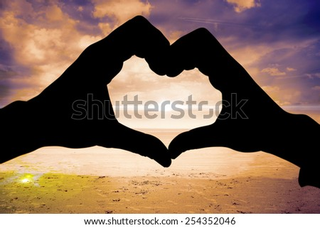 Couple making heart shape with hands against serene beach landscape - stock photo