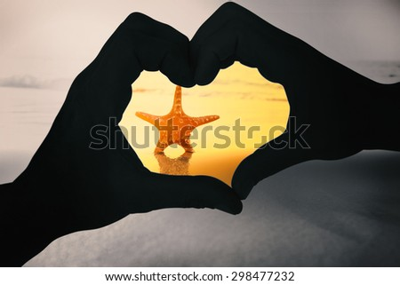 Couple making heart shape with hands against starfish on the sand - stock photo