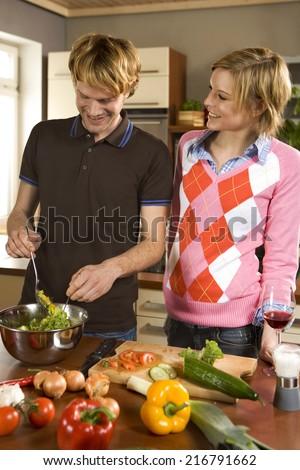 Couple making salad. - stock photo